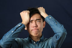 Disappointed young Asian man making face Royalty Free Stock Photos