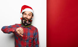 Disappointed young bearded man wearing santa hat Royalty Free Stock Image