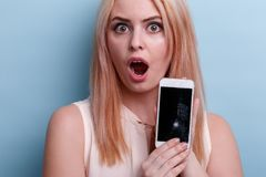 Disappointed girl, holds in hand a broken mobile phone emotionally opening mouth. Blue background. Disappointed young blond girl, European-looking, holds in her royalty free stock photos