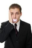Disappointed young businessman with pacifier Royalty Free Stock Photos