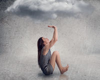 Disappointed young businesswoman with raincloud above her head Stock Photo