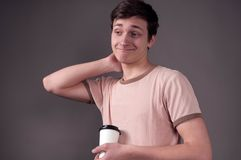 Disappointed young man in beige t shirt standing, scratching head, looking away and holding paper caps with coffee royalty free stock images