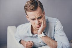 Disappointed young man having toothache. It will be over. Handsome sad young man touching his face and sitting in the sofa while having toothache Stock Images