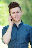 Disappointed young man at telephone Stock Image