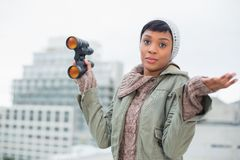 Disappointed young model in winter clothes holding binoculars Stock Photo