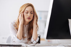 Disappointed young office manager having headache in the office. Suffering from ache. Prostrate exhausted young office manager sitting at the table in the Royalty Free Stock Photography