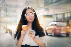 Disappointed Young Woman Holding Smartphone and Coffee Cup Stock Photo