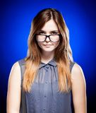 Disappointed young girl looking through the nerd glasses Royalty Free Stock Photos