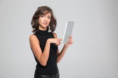 Disappointed young woman using tablet. Disappointed annoyed young woman in black clothes using tablet royalty free stock photo