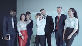 Disappointment of business team. Team of businesspeople standing together in conference room and react to bad news as if just learned inconvenient information stock video footage