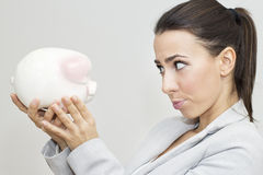 Disappointment businesswoman holding piggy bank Stock Image