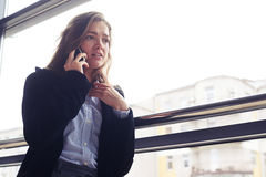 Disappointment female talking on phone. Low angle of disappointment female talking on phone. Sad young woman in black coat against window Stock Photo