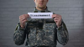 Disarmament word written on sign in hands of male soldier, end of war, peace. Stock footage stock video