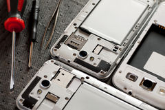 Disassembled cell phone with tools Royalty Free Stock Images