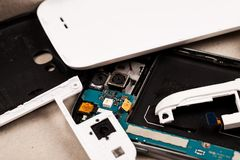 Disassembled cell phones and other gadgets in repair shop.  royalty free stock images