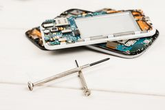 Disassembled cell phones and other gadgets in repair shop.  royalty free stock photos