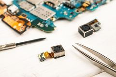 Disassembled cell phones and other gadgets in repair shop.  stock image