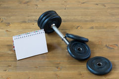 Disassembled dumbbells on a table and a piece of paper. To write Royalty Free Stock Photo