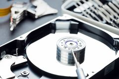 Disassembled hard disk drive inside close-up, spindle, actuator arm, read write head, platter, disassembly tools royalty free stock photos