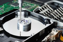 Disassembled hard disk drive inside close-up, spindle, actuator arm, read write head, platter, disassembly tools royalty free stock images