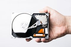 Disassembled hard disk drive in male hand on white background Stock Photography