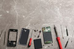 Disassembled mobile phone and repair tools on table, flat lay. Space for text royalty free stock photography