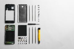 Disassembled mobile phone and repair tools on white background. Top view stock images