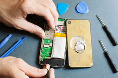 Disassembled mobile phone with repair tools. Workshop Tool Repair Service Device Electronics Damage Maintenance Smartphone Concept Stock Photo