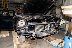 Disassembled old Russian classic car of the representative class produced in the Soviet Union with opened hood without bumper in royalty free stock photo