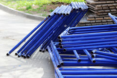 disassembled scaffolding in the form of tubes, painted in blue paint lay beside construction house. Stock Images