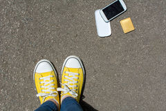 Disassembled smartphone on the ground in front of person Royalty Free Stock Images