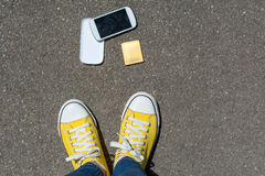 Disassembled smartphone on the ground in front of person Stock Images
