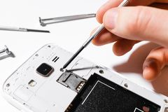 Disassembled white cell phone. Mobile phone repair, screwdriver in the hands of men close-up, white background, isolated stock photography