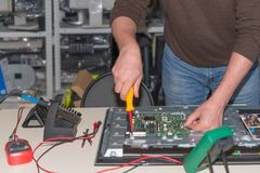 Disassembly and repair of modern LCD TV. Dismantling of the motherboard for diagnostics.  royalty free stock photo