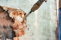 Disassembly of walls and openings with an electric jackhammer, close-up, dust hoarse from under the chisel.  stock image