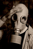 Disaster. A dark image featuring someone wearing a gas mask holding his head Stock Photography