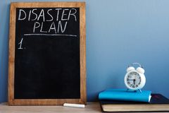 Disaster Plan written on a blackboard and notepads stock photos