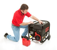 Disaster Preparedness - Power Supply. Man preparing to put gasoline in his 10 horsepower electrical generator.  Isolated on white Royalty Free Stock Images