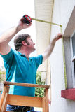 Disaster Ready - Boarding up Window. Man boarding up the windows on his home to prepare for a hurricane or tornado royalty free stock photography