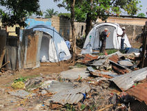 Disaster relief tents erect ed next to badly damaged houses by UK aid workers in Brazzaville, Congo. Royalty Free Stock Photography