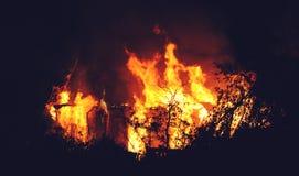 Disastro della natura o di incendio doloso - il fuoco bruciante fiammeggia sul tetto di legno della casa immagini stock