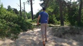 Disattivato appena va sulla sabbia, scala una piccola collina La vista dalla parte posteriore Vacilla, l'uomo zoppica archivi video