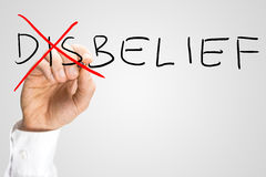 Disbelief - Belief, a concept of opposites. With a man crossing through the Dis of the handwritten word Disbelief on a virtual screen with copyspace Stock Photo