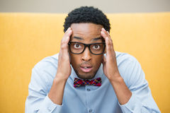 Disbelief. Closeup portrait, stunned nerd young man, hands on head, open mouth jaw drop with bow tie and big glasses, isolated yellow background. Negative human Stock Photos