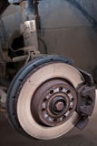 The disc brake of a car made visible by taking of the wheel. A detached wheel of a car makes the disc brake visible Stock Image
