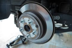 Disc brake rotor and pads on a vehicle royalty free stock photo