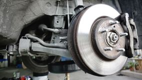 Disc brake of the vehicle for repair, in process of new tire replacement. Car brake repairing in garage. Close up stock photo