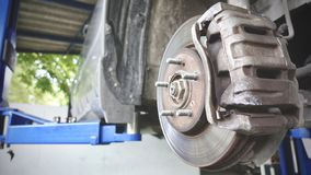 Disc brake of the vehicle for repair, in process of new tire replacement. Car brake repairing in garage. Close up stock image