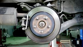 Disc brake of the vehicle for repair, in process of new tire replacement. Car brake repairing in garage. Close up stock photos