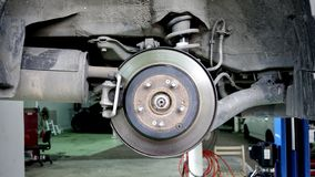 Disc brake of the vehicle for repair, in process of new tire replacement. Car brake repairing in garage. Close up stock photography
